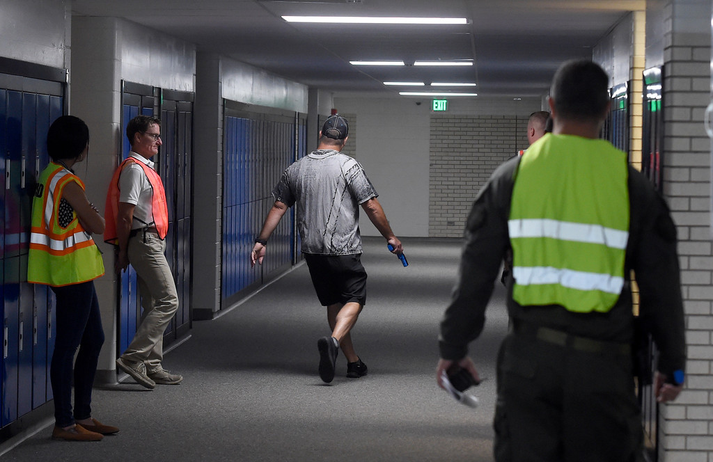 . BROOMFIELD, CO - AUGUST 10: (Photo by Cliff Grassmick/Staff Photographer) Larry Ottosen, playing the part of the active shooter, walks the  Broomfield High School halls during the drill. Broomfield Police Department and Boulder Valley School District held joint training session at Broomfield High School with officers and school staff to cover what everyone should do in an active-shooter situation.