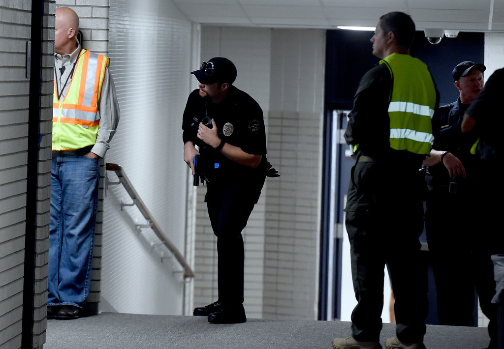 . BROOMFIELD, CO - AUGUST 10: (Photo by Cliff Grassmick/Staff Photographer) A Broomfield Police officer looks down the hall for the shooter during the drill. Broomfield Police Department and Boulder Valley School District held joint training session at Broomfield High School with officers and school staff to cover what everyone should do in an active-shooter situation.