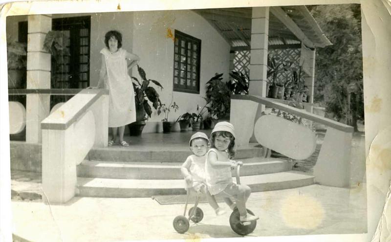 Fernanda e Helena Simões no triciclo. Emilia Simões na varanda.