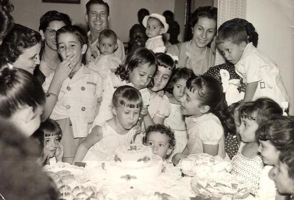 Aniversário Nany Tavares 1958 - 5 anos  Aurora  Tavares a tapar a boca do Joca Fontinhas;Tavares c/Guida ao colo; Teresa Fontinhas (de costas c/rabo de cavalo) ;Zelinha (c/dedo no nariz); Nani Tavares a assoprar as velas;   Isabel Coelho (por trás);as 3 manas  Humberto Sousa:Olga, Betty e Carla, a  mãe Julieta Humberto Sousa atrás delas, Isabel Medeiros, Valdoleiros