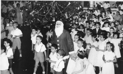 O loirinho à esquerda é o João Manuel Dyson. O Miguel Oliveira está à direita do Pai Natal, em segundo plano. À esquerda do Pai Natal está a Maria João Alho e atrás dela o Jorge Renato Campos. A menina do meio um pouco mais abaixo é a Tereza Misseno Grilo e de lacinho ao pescoço, por cima da cabeça dela o Jorge Mendonça Santos. Atrás parece o Carlos Alberto Bastos. O Joca Sucena està á direita do Jorge M. S. ao pé da árvore de Natal.