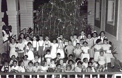 Natal 1953 Em pé, da esquerda para a direita a minha irmã Tininha, o Toni Dinis (filho do Samokinda), atrás a Lurdes Rodrigues (de óculos), a seguir a Nita Feronha e o Zé Luís Feronha, à frente deles não consigo recordar-me,depois João Manuel Dyson, Adão Barata, Bélita Américo Santos, Isabel Dyson (com o boneco), atrás não sei quem é, depois estou eu (Jorge), à minha esquerda está o Hernani Madeira Rosa e a Teresa Misseno e atrás o Jorge Renato Campos, mais atrás o Marco António Olímpio (Pim-pim), o Jorge Leopoldo (que ficou sem um braço num acidente nos baloiços ao pé da casa do pessoal),a Cristalina, das ultimas meninas identifico a última que é a Maria João Alho atras dela a Isa Rosendo. Da malta mais miúda, o Vítor Mário Correia é o segundo, o puto a berrar à direita parece ser o Quim-quim Silva Neves,  a Sara Sernadas é a gordinha do meio e a Carmencita está à sua frente. A menina com o laçarote parece-me a Nélinha Rodrigues (já falecida) e o Carlitos Rodrigues está mesmo por baixo de mim. É claro que também devem estar pelo menos os irmãos de quem já identifiquei mas que não consigo individualizar: ToZé e Zé Manel Américo Santos, Eduarda Olímpio, Nucha Barata, etc.