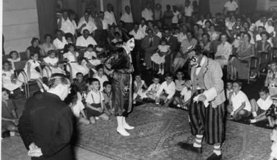 Sentadas à esquerda, a Maria João Alho de lacinho na cabeça e a Tininha Santos. Parece-me a Sara Sernadas no chão aos pés do palhaço rico.