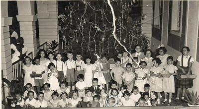 Natal 1953 Em pé, da esquerda para a direita Tininha, o Toni Dinis (filho do Samokinda), atrás a Lurdes Rodrigues (de óculos), a seguir a Nita Feronha e o Zé Luís Feronha, à frente deles não consigo recordar-me,depois João Manuel Dyson, Adão Barata, Bélita Américo Santos, Isabel Dyson (com o boneco), atrás não sei quem é, depois estou eu (Jorge), à minha esquerda está o Hernani Madeira Rosa e a Teresa Misseno e atrás o Jorge Renato Campos, mais atrás o Marco António Olímpio (Pim-pim), o Jorge Leopoldo (que ficou sem um braço num acidente nos baloiços ao pé da casa do pessoal),a Cristalina, a Maria João Alho e a Isa Rosendo (primeira da direita). Da malta mais miúda, o Vítor Mário Correia é o segundo, o puto a berrar à direita parece ser o Quim-quim Silva Neves, a Sara Sernadas é a gordinha do meio e a Carmencita está à sua frente. A menina com o laçarote parece-me a Nélinha Rodrigues (já falecida) e o Carlitos Rodrigues está mesmo por baixo de mim. Bilocas o primeiro da esq/ fila de baixo com um peao na mao.