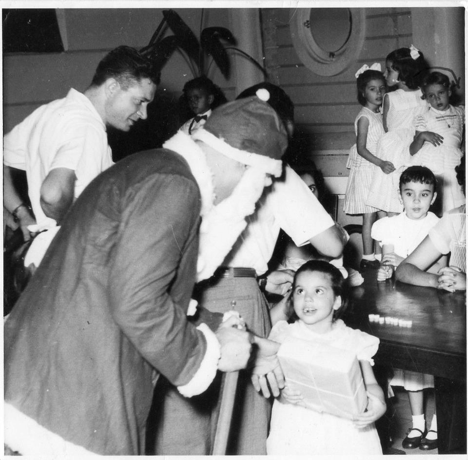 Dundo - Festa de Natal Lisa Teixeira a receber a prenda do pai Natal Eng. Rego ao lado do pai natal Ao fundo a Vanda Rosendo e o Bilocas ( perto da planta)