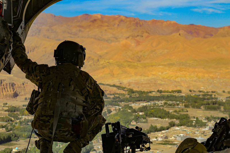 A crew chief overlooks the vast mountain ranges of Southeastern Afghanistan while a CH-47 Chinook assigned to the 1st Armored Division's Combat Aviation Brigade is in flight during an advise and assistance mission Oct. 9 2019. Operation Resolute Support (RS) is a NATO-led mission to train, advise and assist the Afghan National Defense and Security Forces (ANDSF) and institutions to support a political settlement across Afghanistan.<br /> <br /> Army photo by MSgt. Alejandro Licea.