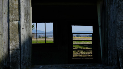 Looking through old barn windows to the fields and mountains in the background