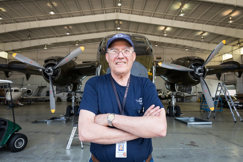 """This is """"Caribou"""" Bob Schrader. He was the crew chief on the very airplane parked behind him, when it flew in Vietnam. He's now a volunteer at the Cavanaugh Flight Museum and helps keep it in working order."""