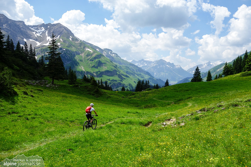 Verdant meadows at the Schrofenpass, offering a pause from technical terrain to enjoy the scenery.