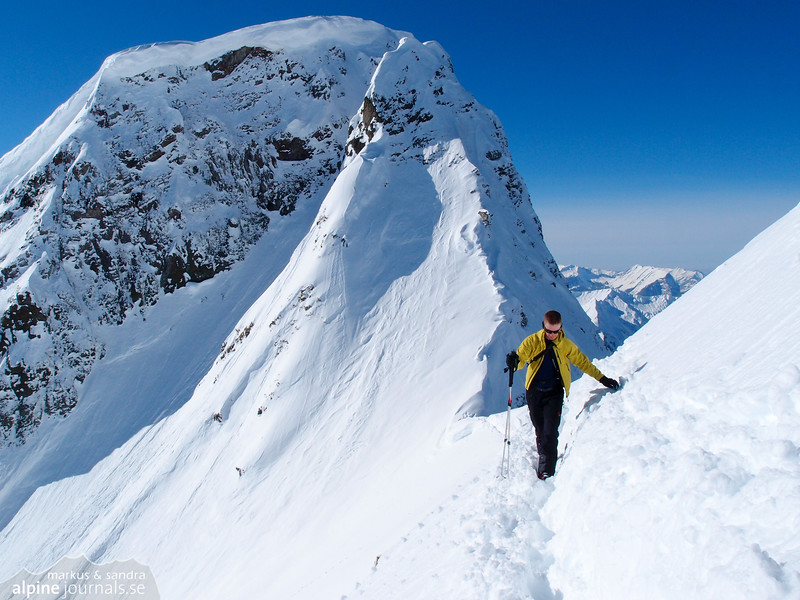 """Markus with Elferkopf main summit behind; just having checked the conditions in the couloir """"Elferrinne""""."""