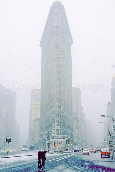 Bike commuter passing New York's Flatiron Building during snowstorm