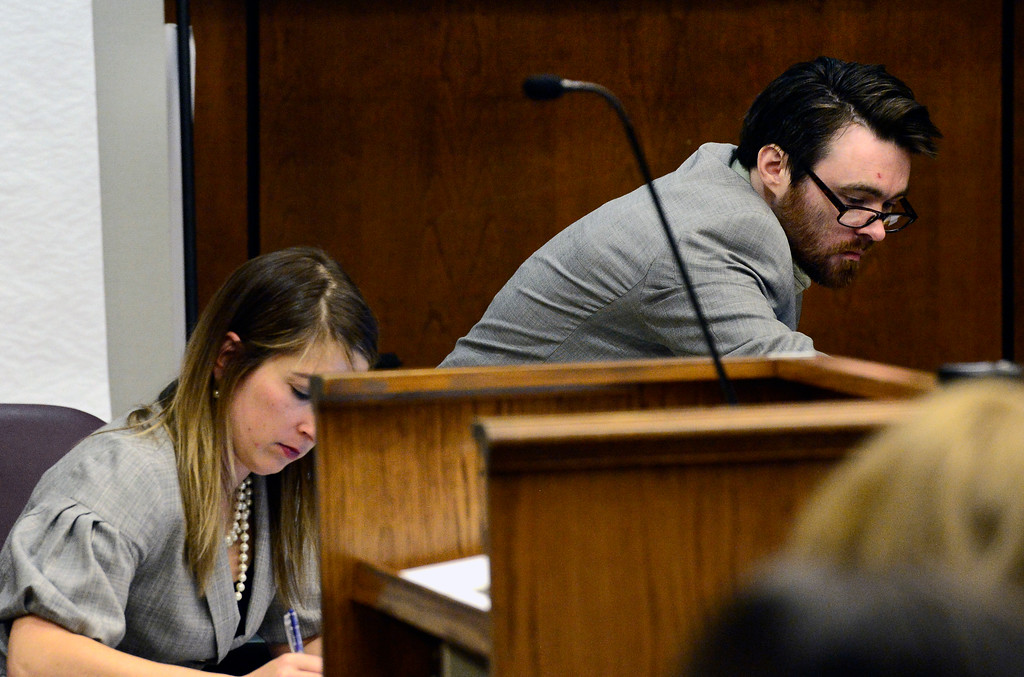 . Adam Densmore reaches across the defense table with his attorney Kathryn Herold on Monday afternoon in the Boulder County Justice Center during Densmore\'s trial were he is accused of murdering his ex-girlfriend, Ashley Mead.  Paul Aiken / Staff Photographer April 16, 2018