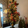 On the table in the dining room sits a gold and red tree.