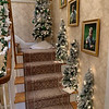 The foyer stairway has flocked trees of white, green and silver.
