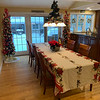 The festive kitchen includes two 6-foot trees, a Christmas tablecloth, a chandelier decorated with greens and ribbon, and a poinsettia for a centerpiece.