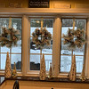 Wreaths of pinecones and berries hang in the kitchen windows.