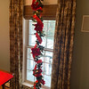 Windows are decorated with garland ribbon and balls.