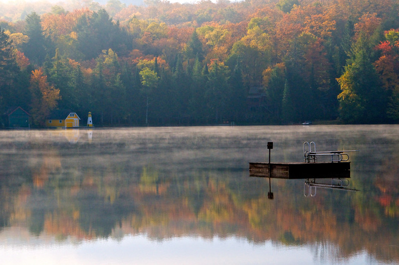 Leaves reflect on the still water of Old Forge Pond