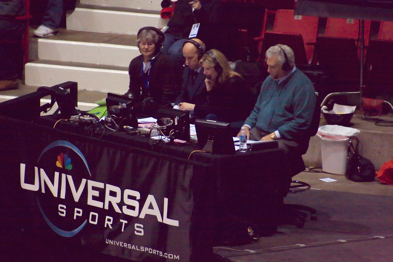 NBC television commentators studying their computer screens during a skater's routine.
