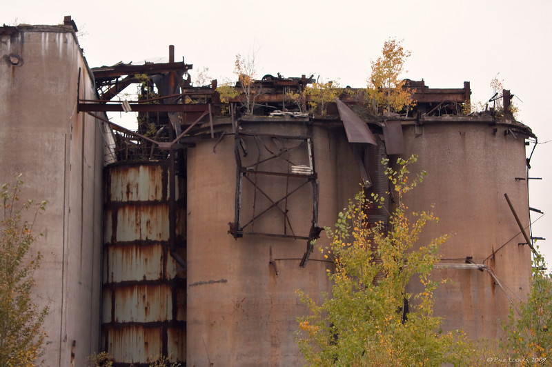 Crushed ore was stored in these silos before being converted into sinter. Sinter was the product of the mine. It was created by combining the magnetite with anthracite coal and powdered limestone. Burners heated the mixture to 1000 degrees Fahrenheit and fused the ingredients into the coarse sinter chunks. The iron-rich material (approximately 63%) was then cooled and shipped off by rail to blast furnaces in Pittsburgh, Aliquippa and Cleveland.