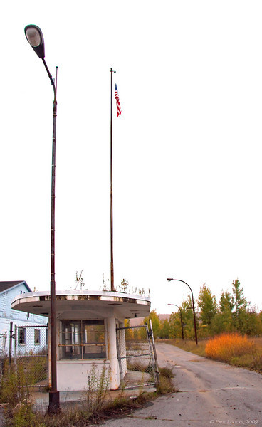 The long-abandoned main entrance guard gate. Old Glory still flies as a symbol of hope and faith for the community of Star Lake.