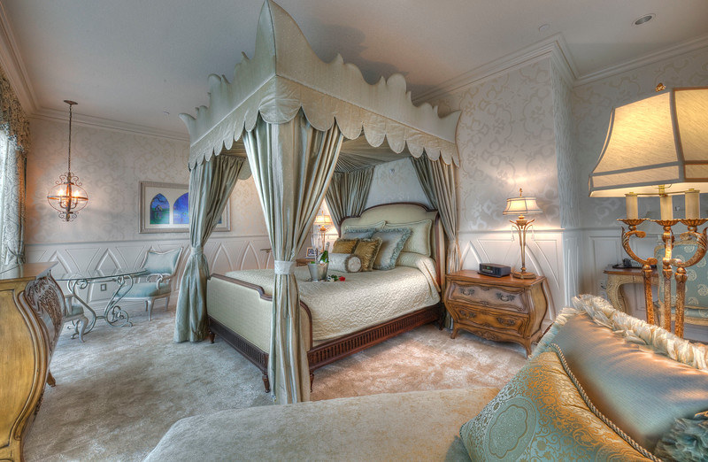 FAIRY TALE SUITE -- A marble foyer descends into an enormous bedroom overlooking the entire resort through floor-to-ceiling windows in the Fairy Tale Suite at the Disneyland Hotel. The sage and champagne colors used throughout the suite elegantly blend the combination of blonde and glass furniture and the suite's centerpiece is an exquisite canopy bed overlooking the corner view. The room is finished with crown moulding, automatic drapes and a custom-designed dresser, from which a flat-panel television ascends at the touch of a button.
