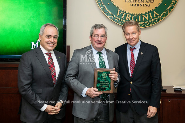 Board of Visitors Vice Rector James W. Hazel receives an award from the Faster Farther Campaign from President Ángel Cabrera, left, and Board of Visitors Rector Thomas M. Davis, right. Photo by:  Ron Aira/Creative Services/George Mason University