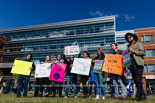 People hold signs during the Future for Fridays climate rally on Merten Lawn at George Mason University. Photo by Lathan Goumas/Office of Communications and Marketing   Photo Taken:Friday, October 18, 2019