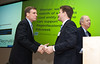 Virginia Senator Mark Warner (L) shakes hands with Greg Werkheiser, Managing Director of the Mason Center for Social Entrepreneurship, at the Mason Center for Social Entrepreneurship's Accelerating Social Entrepreneurship conference at George Mason University's Arlington Campus.