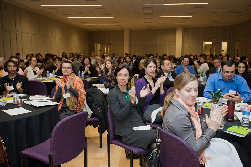 Attendees of the Mason Center for Social Entrepreneurship's Accelerating Social Entrepreneurship conference applaud speakers at George Mason University's Arlington Campus.
