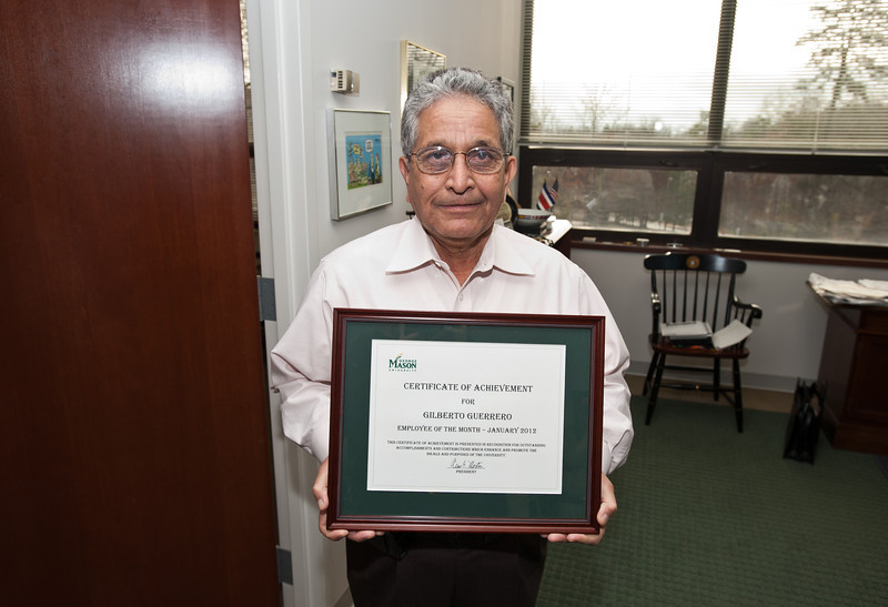 Gilberto Guerrero is awarded his Employee of the Month certificate at a ceremony with Mason President Alan Merten in his office at Mason Hall on Fairfax Campus. Photo by Alexis Glenn/Creative Services/George Mason University