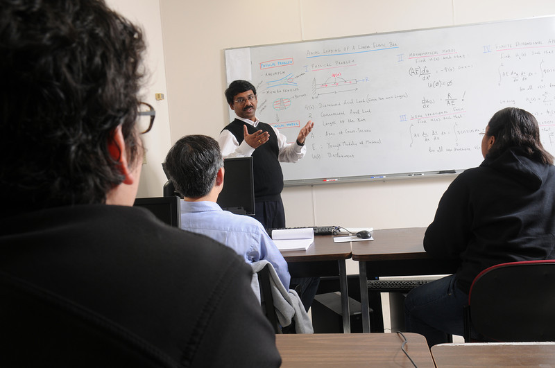 Mathematics faculty, Padhu Seshaiyer, works with students on equations at the white board.