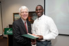 Phil Hunt is presented with a certificate and book during the Legacy Leadership Spring 2012 Cohort closing ceremony with Dr. Alan Merten at Fairfax Campus. Photo by Alexis Glenn/Creative Services/George Mason University