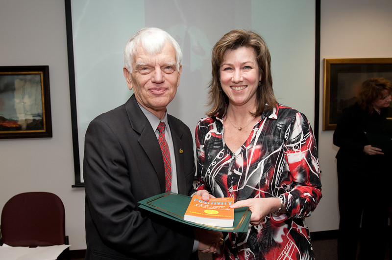 Kim Eby is presented with a certificate and book during the Legacy Leadership Spring 2012 Cohort closing ceremony with Dr. Alan Merten at Fairfax Campus. Photo by Alexis Glenn/Creative Services/George Mason University