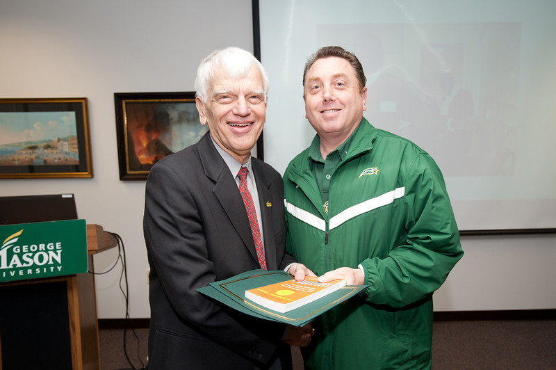 Adam Brick is presented with a certificate and book during the Legacy Leadership Spring 2012 Cohort closing ceremony with Dr. Alan Merten at Fairfax Campus. Photo by Alexis Glenn/Creative Services/George Mason University