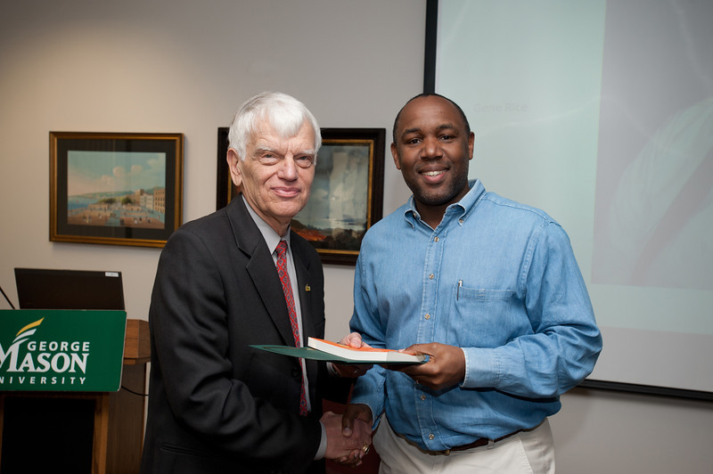 Kevin Clark is presented with a certificate and book during the Legacy Leadership Spring 2012 Cohort closing ceremony with Dr. Alan Merten at Fairfax Campus. Photo by Alexis Glenn/Creative Services/George Mason University