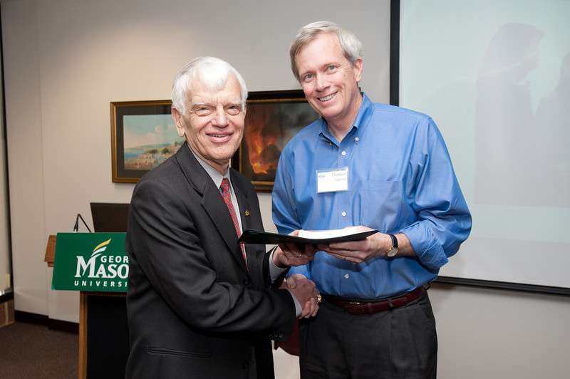 Thomas Calhoun is presented with a certificate and book during the Legacy Leadership Spring 2012 Cohort closing ceremony with Dr. Alan Merten at Fairfax Campus. Photo by Alexis Glenn/Creative Services/George Mason University
