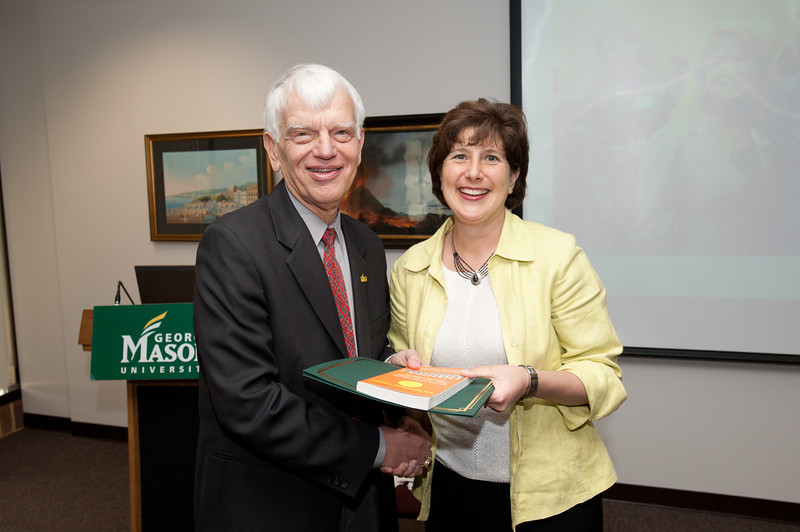 Lisa Gring-Pemble is presented with a certificate and book during the Legacy Leadership Spring 2012 Cohort closing ceremony with Dr. Alan Merten at Fairfax Campus. Photo by Alexis Glenn/Creative Services/George Mason University