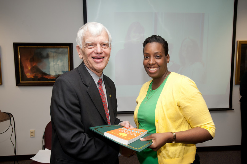 Joy Taylor is presented with a certificate and book during the Legacy Leadership Spring 2012 Cohort closing ceremony with Dr. Alan Merten at Fairfax Campus. Photo by Alexis Glenn/Creative Services/George Mason University, Joy Taylor