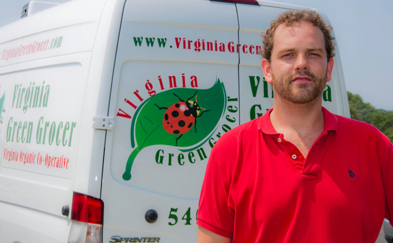 Joshua Graves of Virginia Green Grocer Organic Cooperative, distributes food to Mason faculty and Staff in font of University Hall, Fairfax Campus. Purchasers receive a box of fresh, locally grown, organic produce once a week from late spring through early fall.