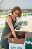 Danielle Wyman, Project Manager, Office of Sustainability, assists the Virginia Green Grocer Organic Cooperative with distributing food to Mason faculty and Staff in font of University Hall, Fairfax Campus. Purchasers receive a box of fresh, locally grown, organic produce once a week from late spring through early fall.