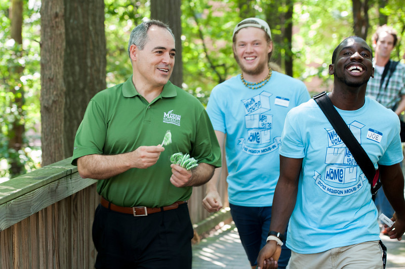 President Ángel Cabrera walks with Housing and Residence Life student move-in staff during Freshman move-in day in the Rappahannock neighborhood at Fairfax campus. Photo by Alexis Glenn/Creative Services/George Mason University