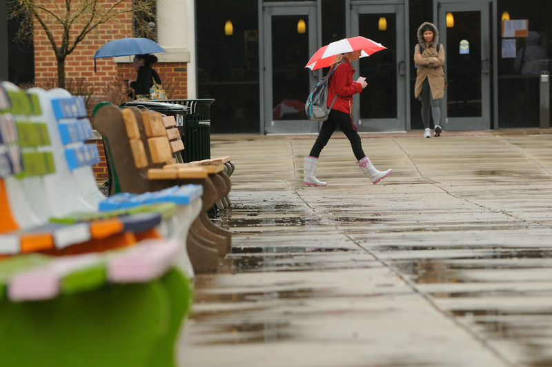 Student walking near Fenwick Library on a raindy day on the Fairfax campus.  Photo by Creative Services/George Mason University