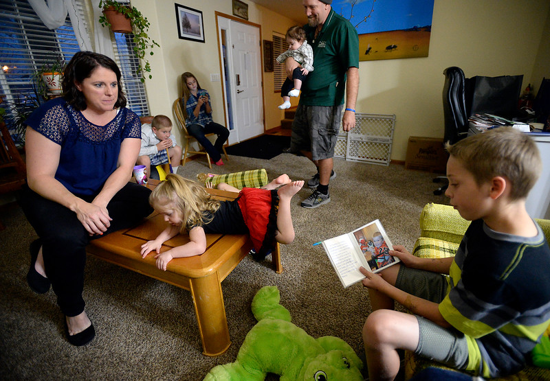 Megan Black, left, holds back tears as her son, Trenton Black, 10, right, reads from a book Monday, Nov. 21, 2016, that the family gave him when they told him they wanted to adopt him. The book introduced all of the members of the family, including pets. Vada Black, 2, front center, Mikey Dawes, 10, left back, and Emily Dawes, 16, back center, hang out as dad, James Black, holds Silas Black, 6 months. Now Trenton is part of a big, loving family, including his younger biological sister Anna Black, 5, not shown. (Photo by Jenny Sparks/Loveland Reporter-Herald)