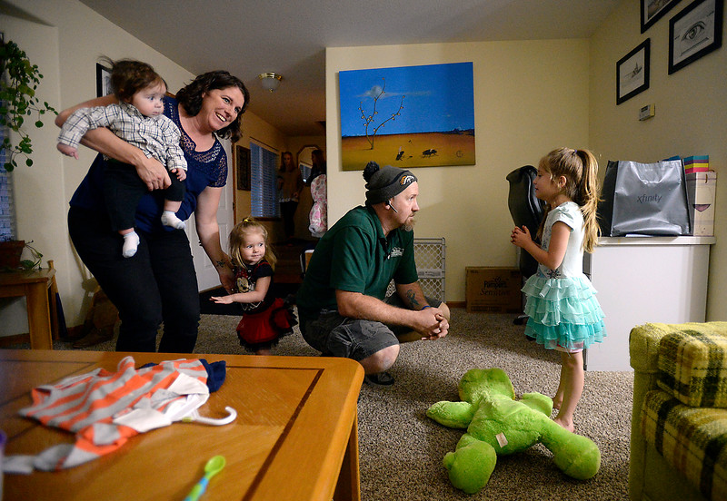 Megan Balck, left, holds Silas Black, 6 months as she puts Vada Black , 2, down while her husband James Black, center, asks Anna Black, 5, if she was good for the babysitter Monday, Nov. 21, 2016, at their Loveland home. (Photo by Jenny Sparks/Loveland Reporter-Herald)
