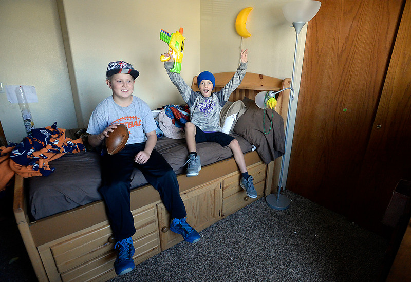 Brothers Mikey Dawes, 10, and Trenton Black pose for a photo Tuesday, Nov. 22, 2016, in Trenton's bedroom of their Loveland home. Trenton and Mikey became friends in first grade and then became brothers a couple of years ago when the Black family adopted Trenton. (Photo by Jenny Sparks/Loveland Reporter-Herald)