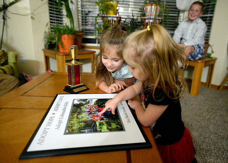 Vada Black, 2, front, and Anna Black, 5, look at a photo of their family Monday, Nov. 21, 2016, on a award they were honored with because they adopted Anna and her brother, Trenton. Brother Mikey Dawes, 10, watches them peek at the photo.  (Photo by Jenny Sparks/Loveland Reporter-Herald)