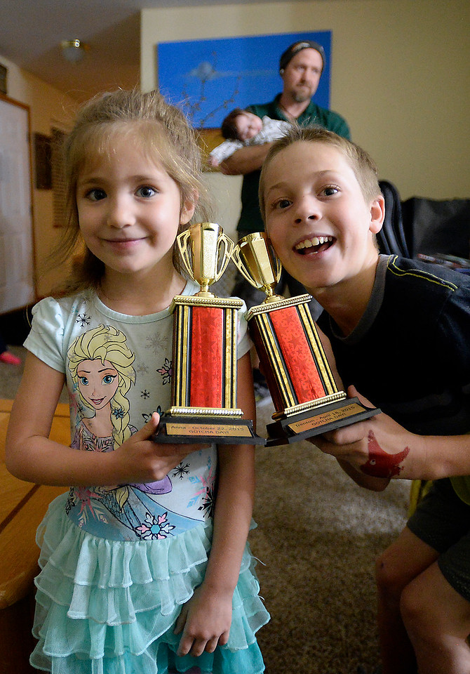 Trenton Black, 10, and his sister, Anna Black, 5, show off their trophies Monday, Nov. 21, 2016, that were given to them to honor the day they were adopted by the Black family in Loveland.  (Photo by Jenny Sparks/Loveland Reporter-Herald)