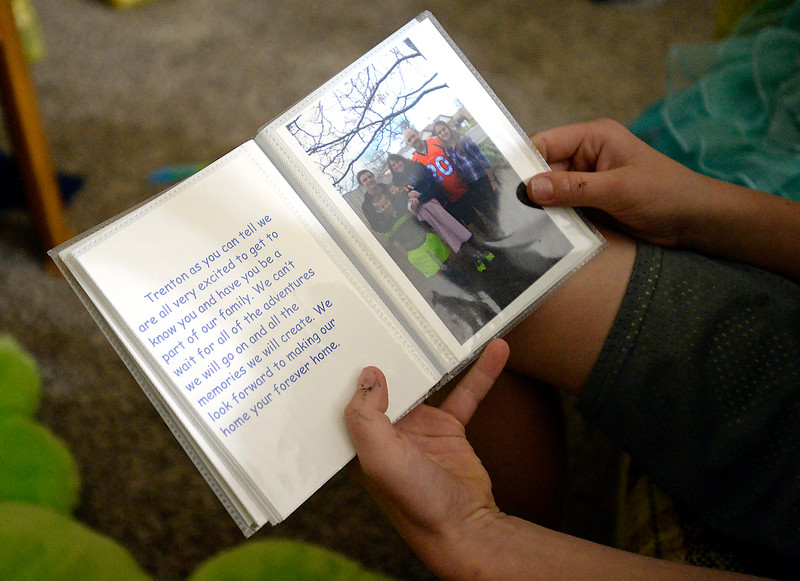 Trenton Balck, 10, reads from a book Monday, Nov. 21, 2016, that was given to him by the Black family when they told him they wanted to adopt him.  (Photo by Jenny Sparks/Loveland Reporter-Herald)