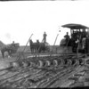 [Three men standing on a tractor plowing a field, near Arcola, between 1910 and 1914]